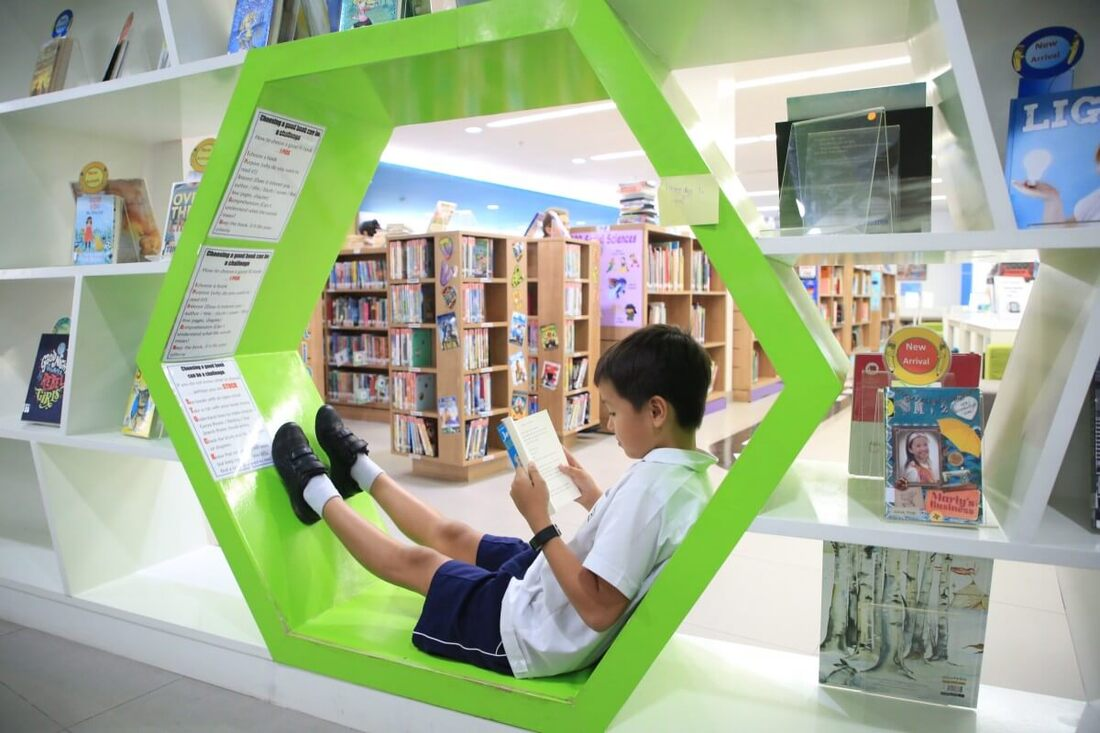 Child reading book in library.
